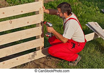 homme, clôture bois, bâtiment