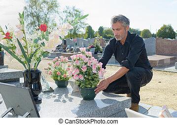 homme, déposer, fleurs, sur, a, tombe