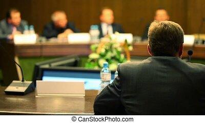 homme, dans, costume, asseoir, table, sur, conférence