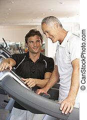 homme, fonctionnement, à, entraîneur personnel, sur, machine courante, dans, gymnase