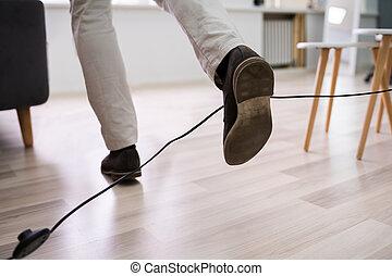 homme, jambes, corde électrique, trébucher