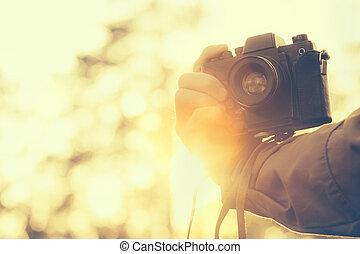 homme, possession main, retro, appareil-photo photo, extérieur, hipster, style de vie, à, coucher soleil, lumières, arriere-plan, pellicule, couleurs