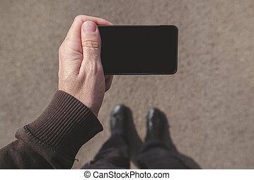 homme, regarder, smartphone, écran, marchant, sur, rue