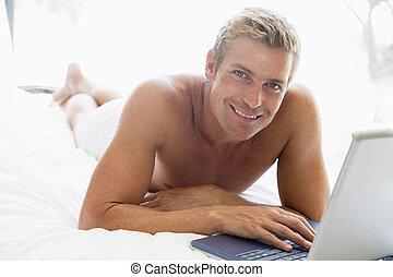homme, situer dans lit, à, ordinateur portable, sourire