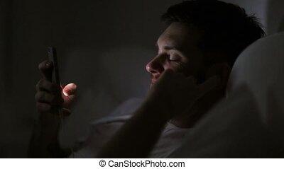 homme, smartphone, écouteurs, lit, nuit