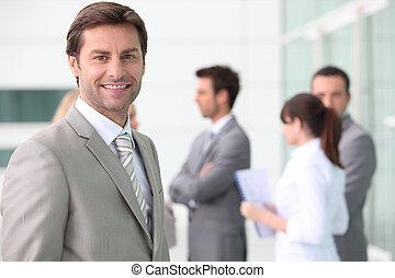 homme souriant, à, collègues, dehors, bâtiment bureau
