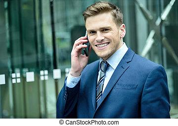 homme souriant, dans, complet, conversation, sur, cellphone
