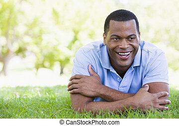 homme souriant, mensonge, dehors