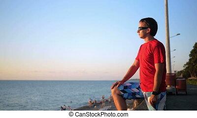 homme, tête, sien, tourner, mer, délassant, après, jeune regarder, sunset., appareil photo, coucher soleil, admire, water., lunettes soleil, il, plage, beau