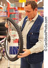 homme, tient, courbé, roue bicyclette, dans, magasin