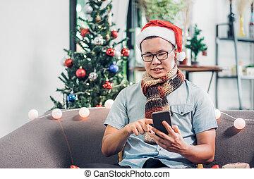 homme, usage, hiver, fête, mobile, partie., gens, amis, arbre, asiatique, appeler, usure, santa, maison, séance, vacances, venir, noël, sofa, chapeau