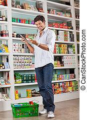 homme, vérification, liste épicerie, dans, supermarché
