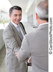 hommes affaires, serrer main, dehors, bâtiment