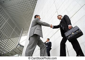 hommes affaires, serrer main, dehors