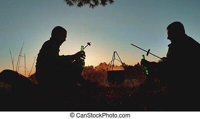 hommes, silhouette, camping, nature, brûler, style de vie, boisson, deux, chaudron, vacances, capot, lumières, bière, saucisses, lumière soleil, dehors, fête, séance, touristes, feu, sunset.