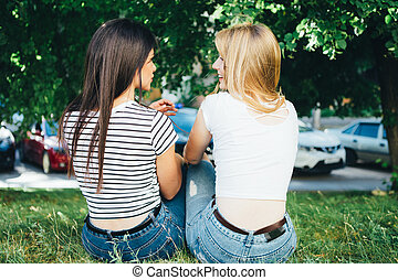 Homosexual women embrace and laugh while sitting on the grass.