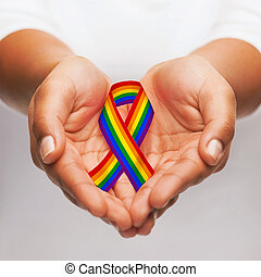 hands holding rainbow gay pride awareness ribbon