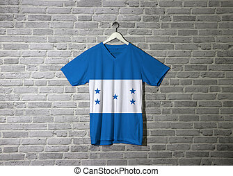 Honduras flag on shirt and hanging on the wall with brick pattern wallpaper
