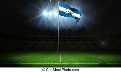 Honduras national flag waving on flagpole against football...