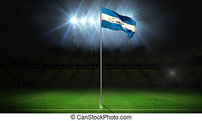 Honduras national flag waving on flagpole on football pitch...