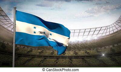 Honduras flag waving on flagpole in football stadium with flashes