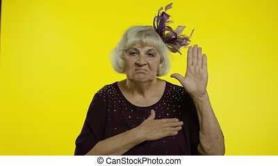 Honest responsible senior old woman raising hand, touching chest and taking vow, saying promise, swear, looking at camera trustworthy reliable. Elderly lady grandma on yellow background. 6k footage