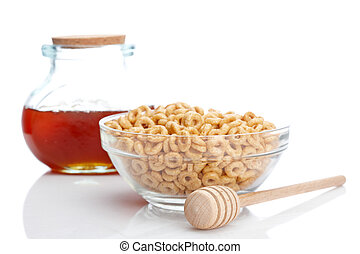 Honey jar, wooden drizzler and glass bowl of cheerios, reflected on white background