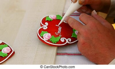 Honey cake writing - Man\'s hand writing on honey cake with...