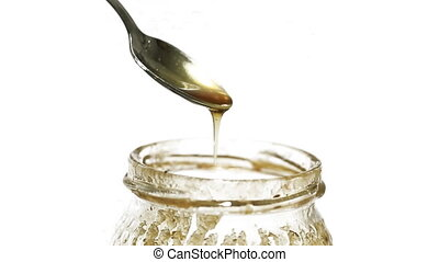 Honey - Closeup view of silver spoon with honey, white...