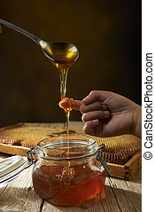 Honey dripping from a spoon on young finger