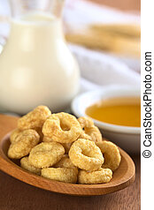 Honey flavoured cereal loops on wooden spoon with milk and honey in the back (Selective Focus, Focus on the front of the loops in the front)