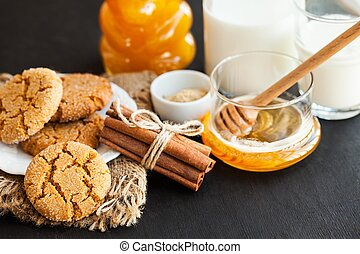 Honey ginger cookies with milk on a black background