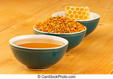 Honey, honeycomb and pollen in bowls - Honey, honeycomb and ...