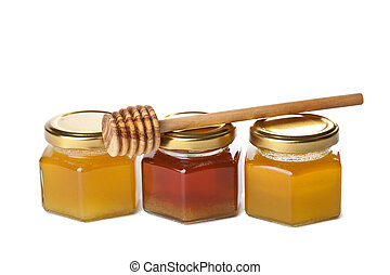honey in bottles and wooden dipper isolated