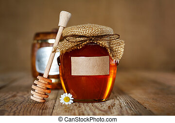 Honey in glass jar on a wooden background
