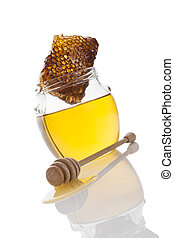 Honey in glass jar with wooden honey spoon and honey comb...