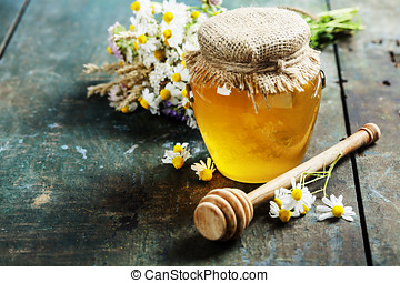 Honey jar and dipper on wooden background