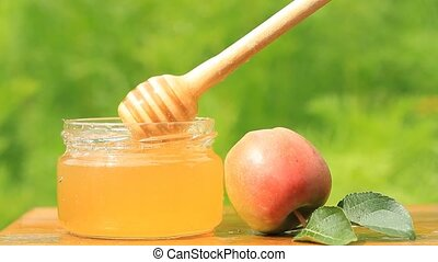 Honey jar, stick and apple on wooden table