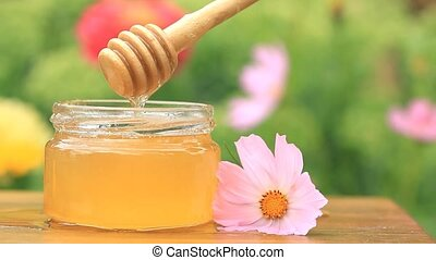 Honey jar, stick and flower on wooden table.