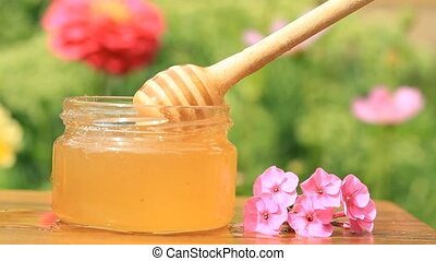 Honey jar, stick and pink flower on wooden table