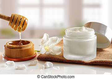 Open glass pot with honey moisturizer isolated on white glass table. Flower, stones, burlap and cane with honey container decoration. Front view with background windows