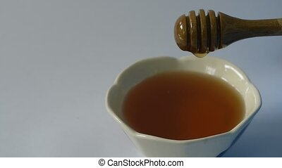 honey on wooden scoop drop to cup in white background