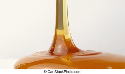 Honey Poured On Plain Background - Closeup of honey pouring...