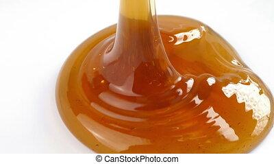 Honey Poured On White Surface - Honey pours onto plain white...