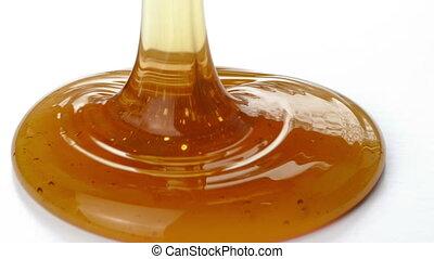 Honey Pouring Closeup - Closeup of honey pouring onto plain...