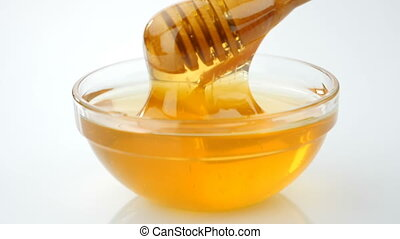 Honey pouring from drizzler into the bowl - Honey pouring...