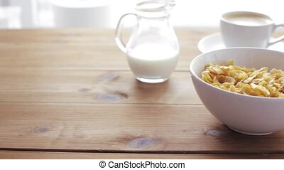 honey pouring to corn flakes on wooden table - breakfast,...