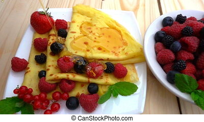 honey pours on pancakes with raspberries, blueberries and...