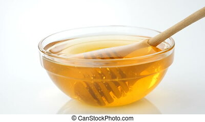 Honey spoon dipped in honey in slow motion