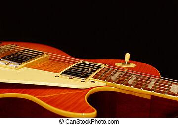 Honey sunburst electric jazz guitar closeup on black background. Shallow depth of field.